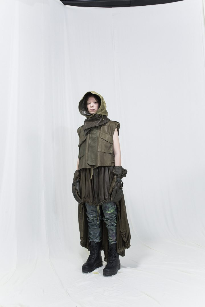 Model is wearing a multicoloured leather vest with matching hood, gloves and skirt, with glossy trousers underneath