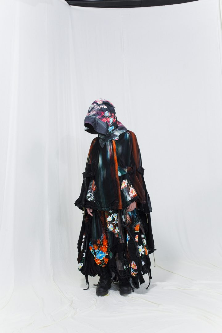 Model is wearing a multicoloured melting floral cape and skirt in velvet, matching hood