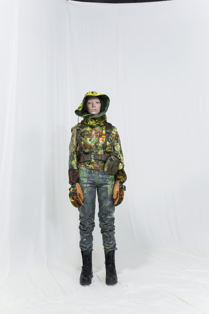 Model is wearing a glossy multicoloured floral jacket with a matching hood, floral gloves and shiny trousers
