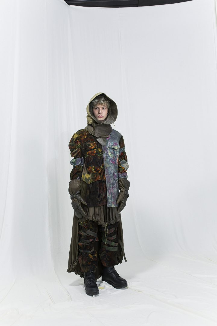 Model is wearing a multicoloured floral jacket with panels, leather hood and bondage velvet trousers underneath