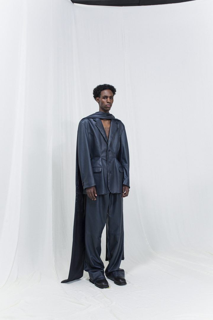 Model is wearing a metallic dark blue blazer and matching oversized trousers.