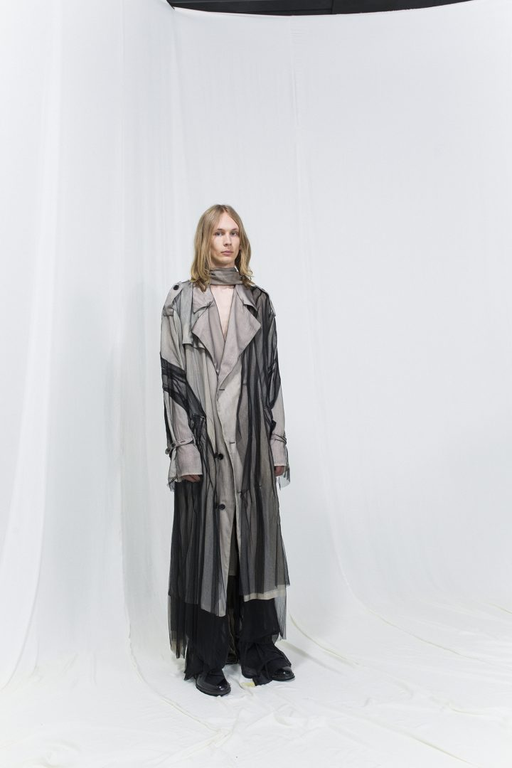 Model is wearing a beige trench coat with black mesh draped on it. Underneath black trousers
