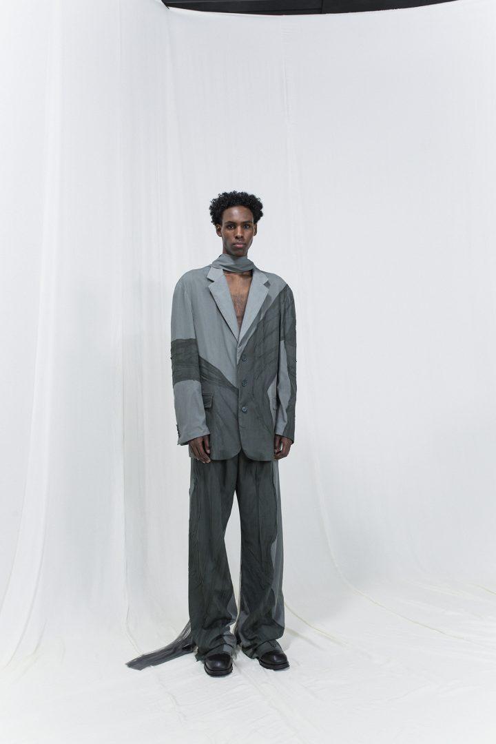 Model is wearing a light grey blazer with dark grey sheer details and flowy dark grey trousers