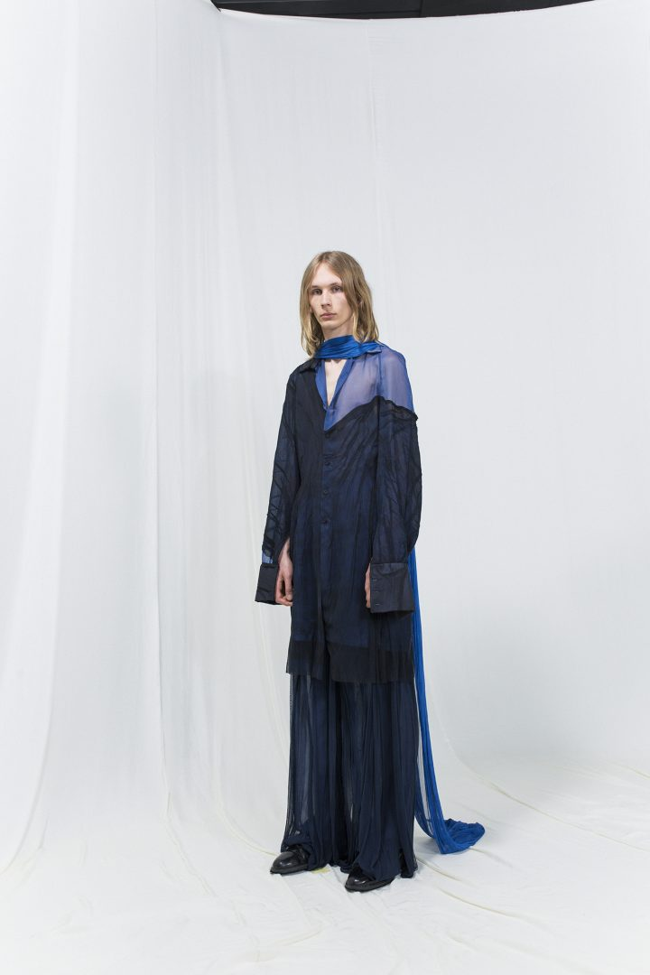 Model is wearing a long coat with sheer blue details and matching navy-blue flowy trousers
