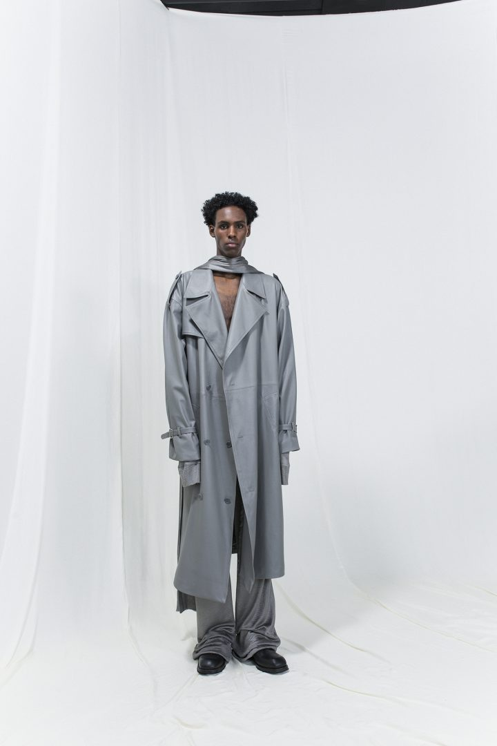 Model is wearing a long silver grey trench coat with matching trousers