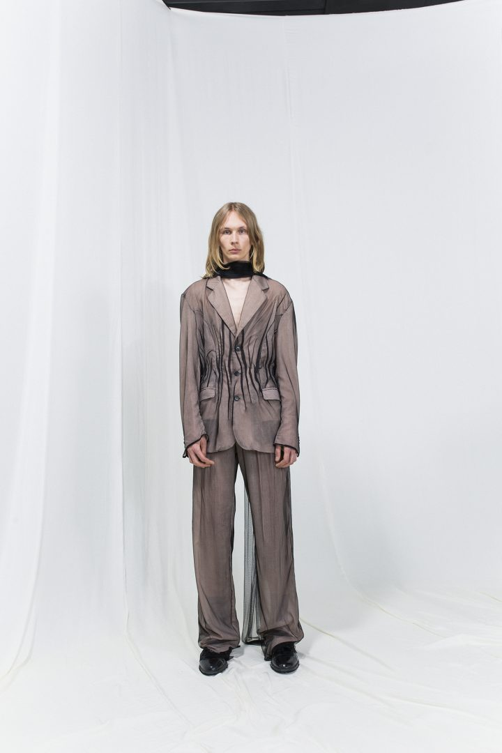Model is wearing a beige blazer with black mesh over it. Matching trousers