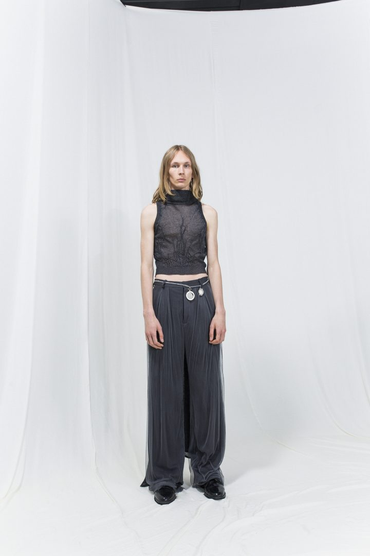 Model is wearing a dark grey metallic knitted top with flowy grey trousers