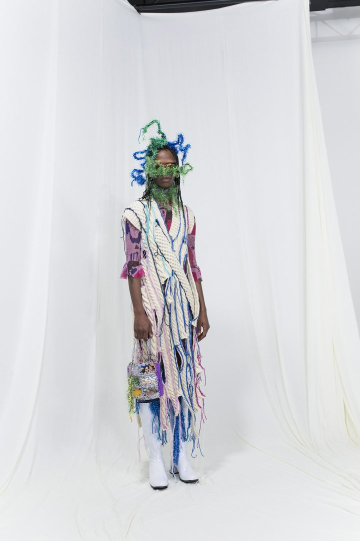 model wearing a white knitted dress with colourful crochet seams, crochet bag, sunglasses and a fringed headpiece