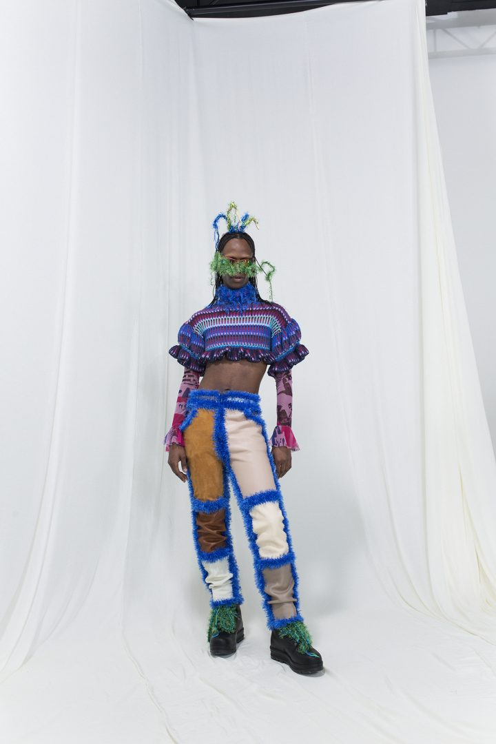 Model wearing a knitted stripe crop-top with crochet leather trousers, mesh top underneath, sunglasses and a fringed headpiece