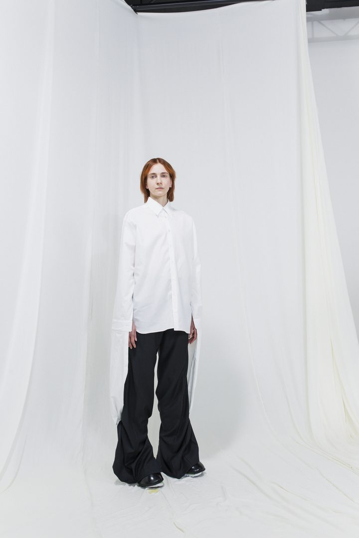 Model wearing an oversized white shirt with oversized black trousers