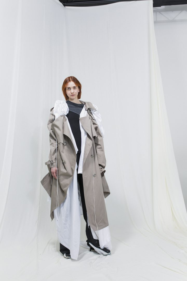 Model wearing a beige trench coat on top of a white robe, black trousers