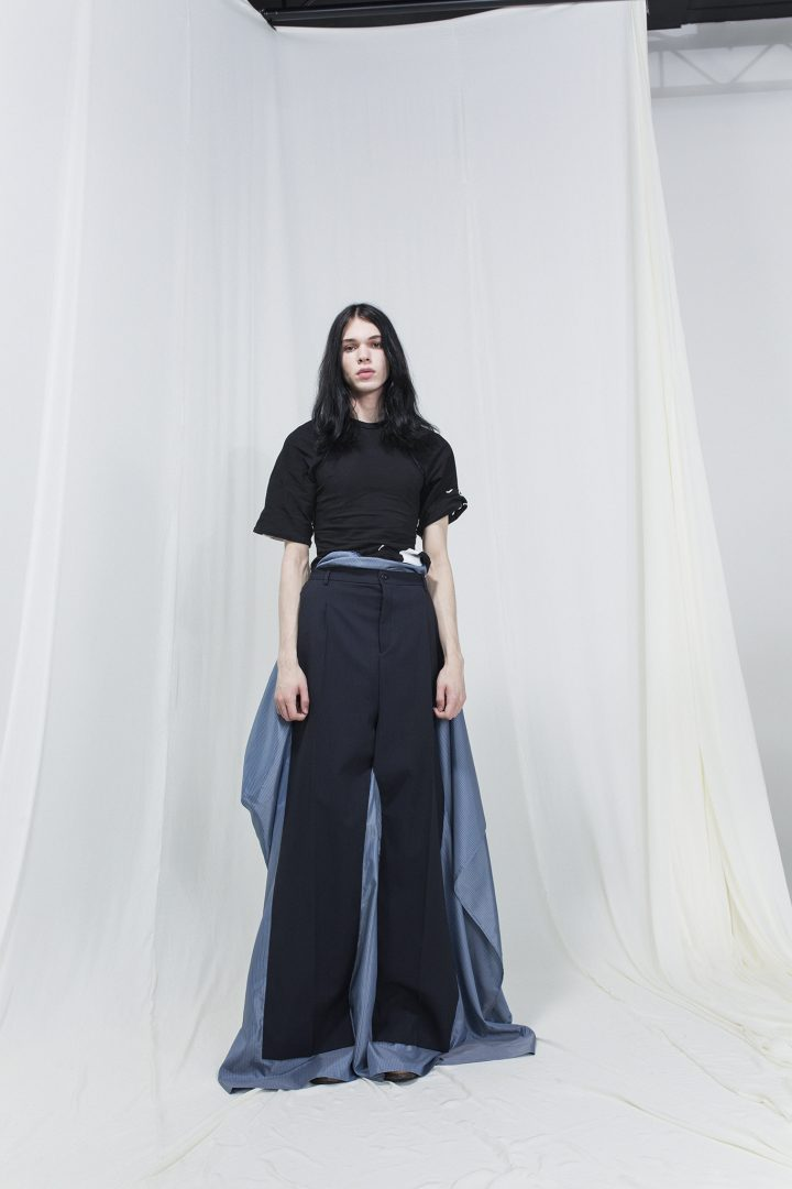Model wearing a black t-shirt with gray-blue skirt with trousers on top