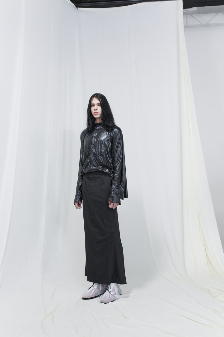 Model wearing a shiny draped shirt with a skirt resembling a pair of trousers