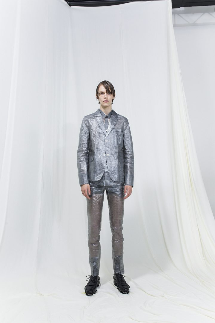 Model wearing silver suit jacket and matching trousers