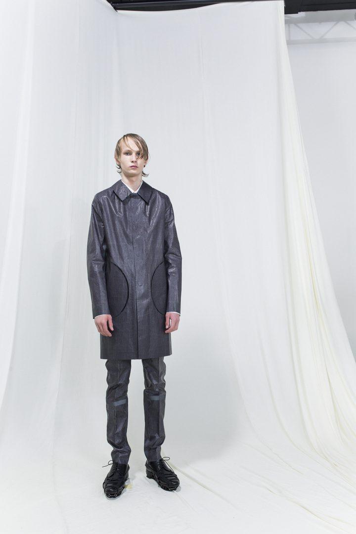 Model wearing dark grey longer jacket with trousers