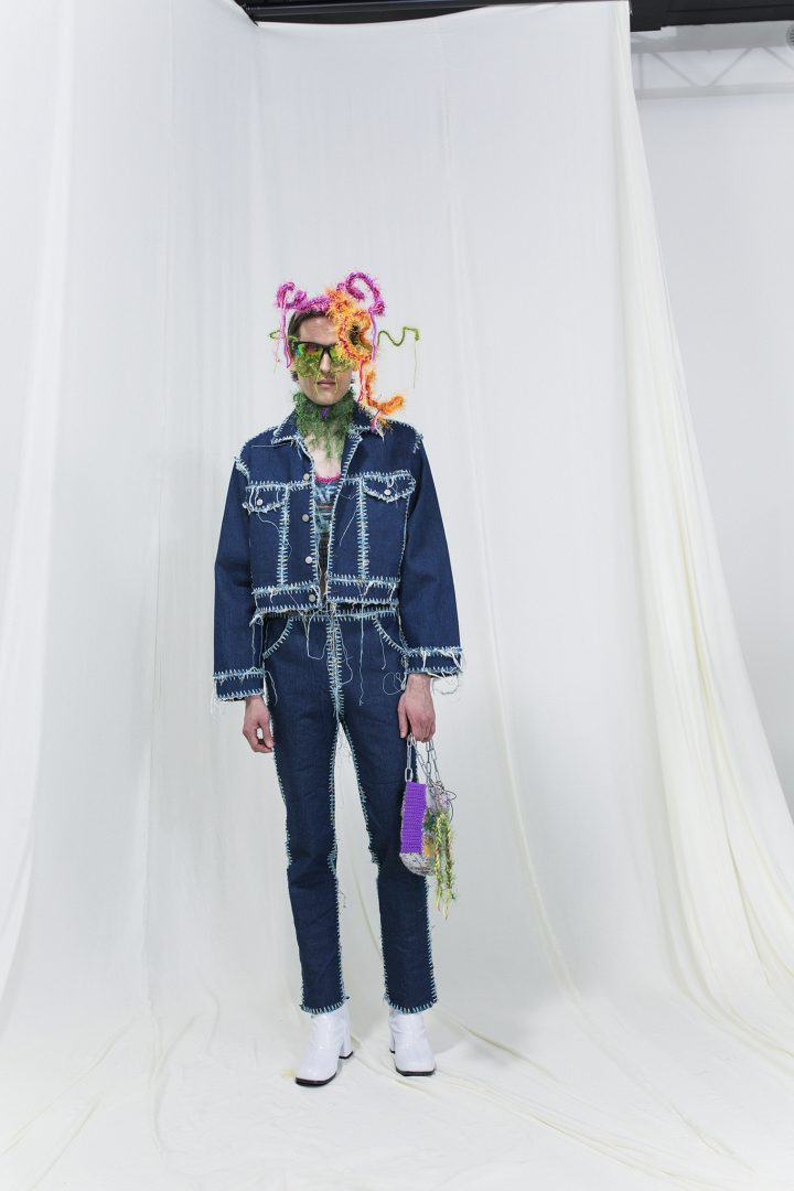 Model wearing a crochet denim jacket and jeans, knitted bag and sunglasses, fringe headpiece